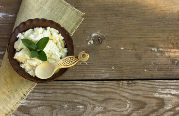 Organic Sour cream and Cottage Cheese in a white ceramic bowl on the kitchen table. Dairy products for the healthy breakfast. Homemade natural cottage cheese prepared from organic dairy products.