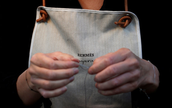 """A leather craftswoman works on a Hermes luxury good displayed during the """"Hermes hors les murs"""" event in Paris"""