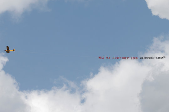 A banner towed by an airplane flies over Lawrenceville
