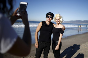 """Erik Smith, 31, and Deb Foster, 30, pose for a photo before surfing dressed as characters from """"Grease"""" during the ZJ Boarding House Haunted Heats Halloween Surf Contest in Santa Monica"""