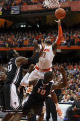 Syracuse Orange guard Scoop Jardine takes a shot over Providence Friars forward Brice Kofane (L) and forward Kadeem Batts during the first half of their NCAA men's basketball game in Syracuse, New York