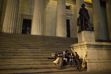 Occupy Wall Street protesters read a book on the steps of Federal Hall in New York