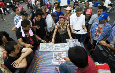 Anti-government 'red shirt' protesters read morning newspapers inside their barricaded encampment in Bangkok's financial district