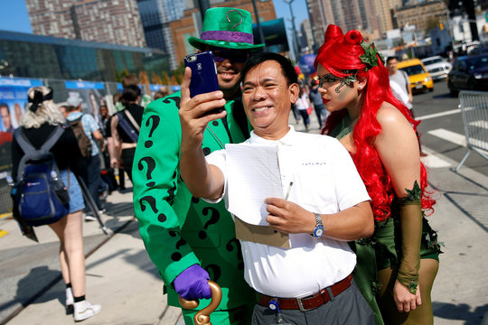 A man takes a selfie with David Gonzalez, dressed as the Riddler, and Chloe Cofresi, dressed as Poison Ivy, outside New York Comic Con in New York