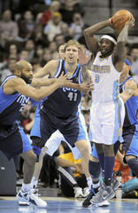 Nuggets' Lawson looks to pass while being pressured by Mavericks' Carter and Nowitzki during their NBA Basketball game in Denver