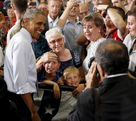 Young boys pose for a photo with Obama as he greets his audience after speaking about the economy during a visit to the University of Wisconsin La Crosse