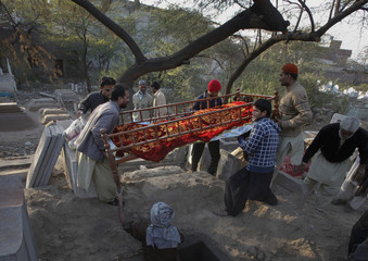 Family members lower the body of 62-year-old heart patient Chaudhry Mohammad Gulab during his burial in Lahore