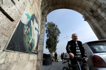 A man pushes a bicycle past a picture of Syria's President Bashar al-Assad at Bab Sharqi entrance near the Jobar district of Damascus