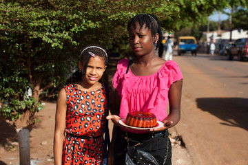 Girls pose for a picture holding a cake in Bissau