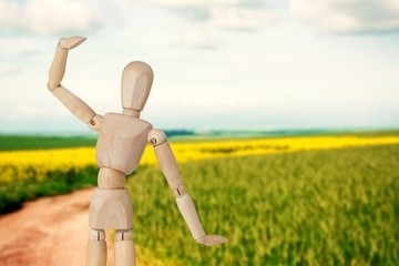 Composite image of wooden 3d figurine standing with hand raised