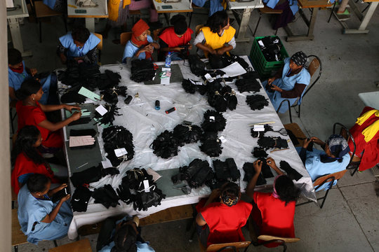 Women sit round the table as they work inside the Pittards world class leather manufacturing company in Ethiopia's capital Addis Ababa