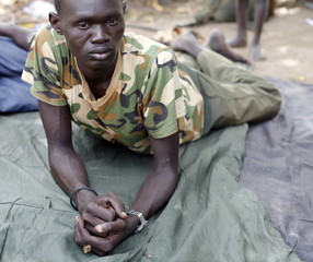 Injured South Sudan SPLA soldier lies outside a hospital in Bentiu
