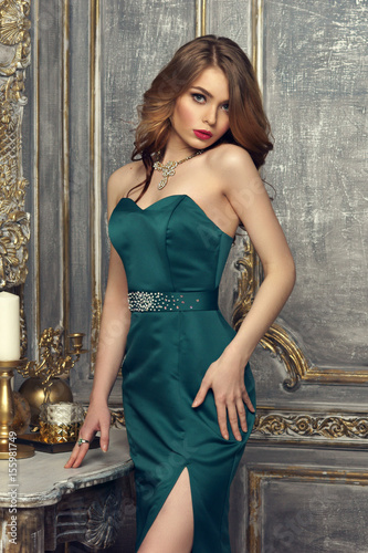 Elegant Red Hair Girl With Curls In Green Mermaid Gress Sitting On Table In Luxury Interior And