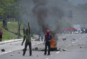 Peasant farmers block an avenue with a burning tire during a protest near the Supreme Court in Tegucigalpa