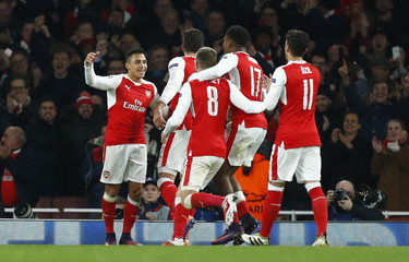 Arsenal's Alexis Sanchez celebrates with teammates after Paris Saint-Germain's Marco Verratti scores an own goal and the second goal for Arsenal