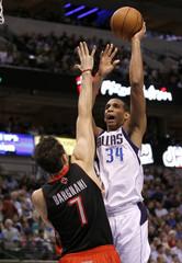 Dallas Mavericks center Brandan Wright shoots over Toronto Raptors center Andrea Bargnani during their NBA basketball game in Dallas