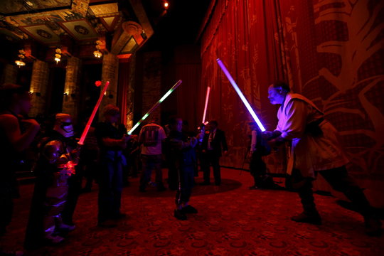 "Moviegoers use their light sabers before the first showing of the movie ""Star Wars: The Force Awakens"" at the TCL Chinese Theatre in Hollywood"