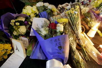 A card with an image of the Eiffel tower is placed next to flowers during a memorial tribute to the victims of Friday's attacks in Paris, at the French Embassy in Beijing