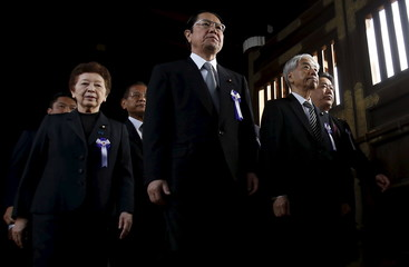 A group of lawmakers including Japan's ruling Liberal Democratic Party lawmaker Otsuji are led by a Shinto priest as they visit to pay their respects to the war dead at the Yasukuni Shrine in Tokyo