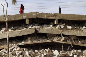 A woman stands with a girl on the ceiling of the ruins of a school bombed by Shi'ite militants of the Shi'ite al-Houthi group during recent conflicts against local tribes in the Hamdan area west of the Yemeni capital Sanaa