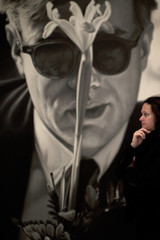 """A worker stands by the painting titled """"Andy Warhol (with flower)"""" by artist Dennis Hopper during the inauguration of the """"Dennis Hopper. On the road"""" exhibition at the Picasso Museum in Malaga"""