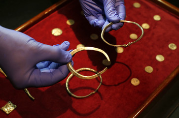 A curator holds silver arm-rings that metal-detectorist, James Mather, discovered as part of a Viking Hoard, which  included silver ingots and rare coins of King Alfred of Wessex and King Ceolwulf II of Mercia, at the British Museum London