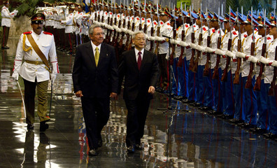 Vietnam's Communist Party General Secretary Trong reviews honor guard with Cuba's President Castro in Havana