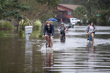 People ride their bikes through flood waters on Rosewood Drive in Myrtle Beach, South Carolina