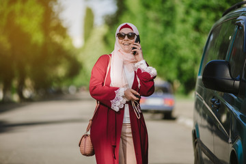 pretty muslim woman use a cellphone at park