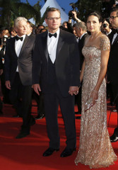 Cast members Douglas Damon and his wife Luciana Barroso leave after the screening of the film Behind the Candelabra in competition during the 66th Cannes Film Festival