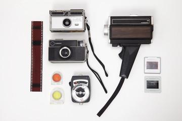 Cámaras y fotómetro vintage organizadas sobre una mesa