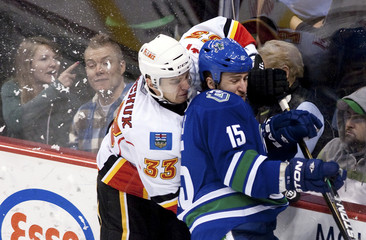 Calgary Flames' Anton Babchuk checks Vancouver Canucks' Tanner Glass during the second period of their NHL hockey game in Vancouver