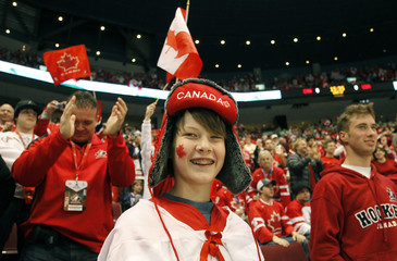 A spectator smiles before the start of the Canada U.S. hockey game at the Vancouver 2010 Winter Olympics