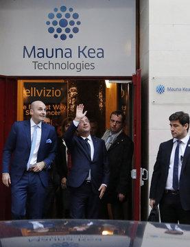 French President Hollande waves near Mauna Kea Technologies CEO Loiseau after a presentation of Cellvizio, a Medical Endomicroscopy virtual assistant at Mauna Kea Technologies office in Paris