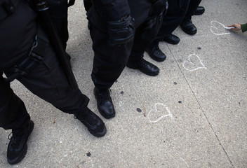 A demonstrator draws hearts with chalk in front of police during an anti-NATO protest in Chicago