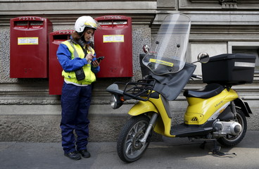 A postwoman use her device in front of headquater of Poste Italiane downtown Milan