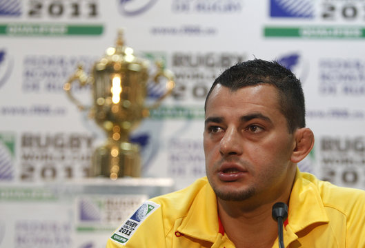 Romania's rugby team captain Socol listens to questions during a news conference as the Webb Ellis Cup trophy is displayed in the background in Bucharest