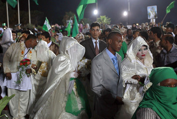 Brides and grooms arrive after a mass wedding ceremony at an area in Bab al-Aziziyah compound in Tripoli