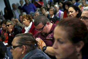 People pray during an interfaith service for all the migrants who have died at sea while attempting to reach European soil at a church in Madrid
