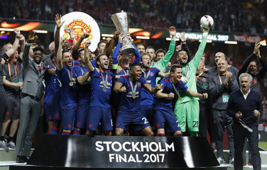 Manchester United celebrate winning the Europa League with the trophy