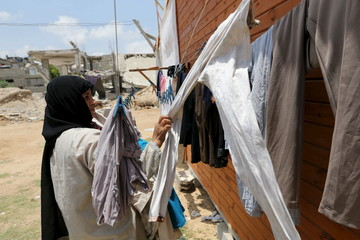 Palestinian woman collects laundry near the ruins of her house, that witnesses said was destroyed by Israeli shelling during a 50-day war last summer, in Khan Younis in the southern Gaza Strip