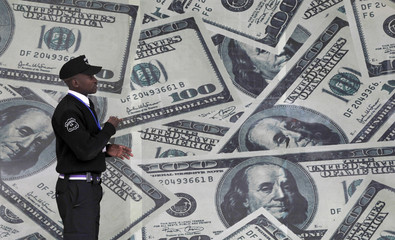 A security guard walks past a montage of U.S. $100 dollar bills outside a currency exchange bureau in Nairobi