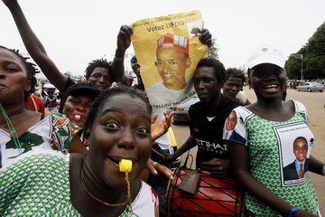 Supporters of Union des Forces Democratiques de Guinea (UFDG), hold a poster of their leader, former Prime Minister and presidential candidate Cellou Dalein Diallo during a presidential campaign rally in Conakry