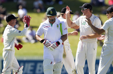 South Africa's Jacques Kallis leaves the pitch after being dismissed by New Zealand's Mark Gillespie, as New Zealand celebrate in the background, on day two of the second international cricket test match in Hamilton