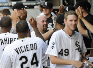 Chicago White Sox hitter Youkilis is congratulated by his teammates after hitting a two-run homer against the Texas Rangers in the first inning of their MLB baseball game in Chicago