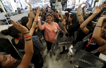The first shoppers are welcome by workers as they enter the newly opened Hennes & Mauritz (H&M) store in Peru, at the Jockey Plaza mall in Lima