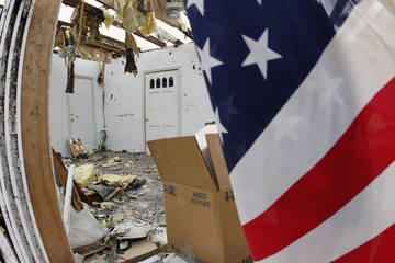 An American Flag hangs on the side of a tornado damaged house in Henryville