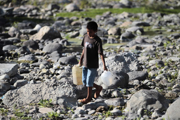 A boy collects water from the polluted Waswali River, near Matagalpa