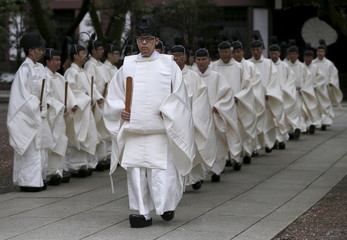 Shinto priests walk toward to the main shrine for a ritual to cleanse themselves during Annual Spring Festival at the Yasukuni Shrine in Tokyo