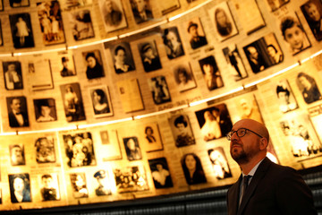 Belgian Prime Minister Charles Michel looks at pictures of Jews killed in the Holocaust during a visit to the Hall of Names at Yad Vashem's Holocaust History Museum in Jerusalem